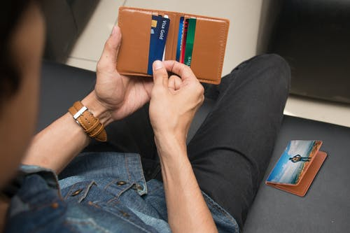 Close-Up Shot of a Person Holding a Brown Wallet with Credit Cards