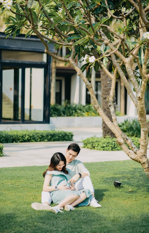 Romantic Asian pregnant couple sitting on street lawn