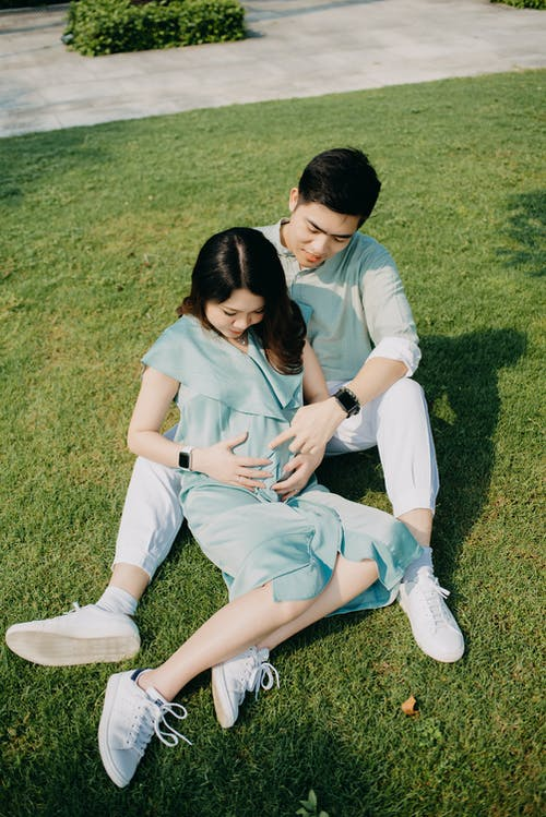 Full body positive young Asian man resting on grassy lawn and touching pregnant wife belly on clear summer day