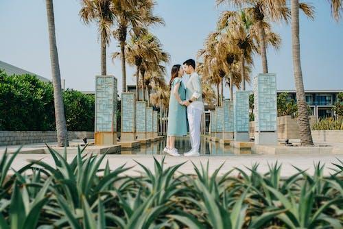 Loving Asian couple holding hands near fountain in modern resort