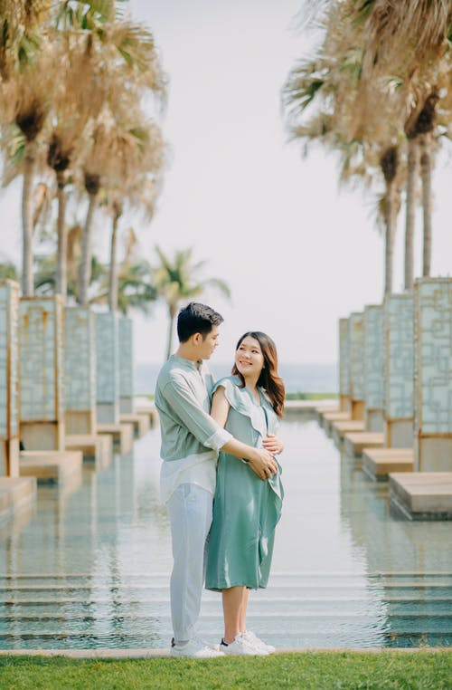 Cheerful Asian man hugging pregnant wife near pool in park