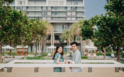 Side view cheerful young Asian couple holding hands and looking at camera while standing in sunny city park
