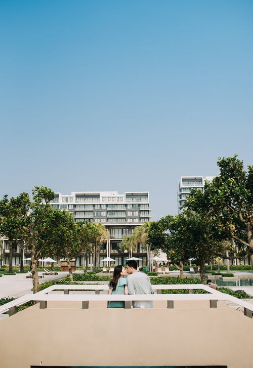 Back view of gentle couple sitting close and kissing each other in park of hotel during vacation