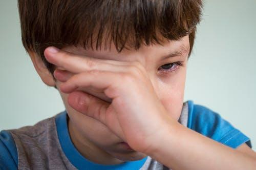 Boy Wiping Tears from Eye