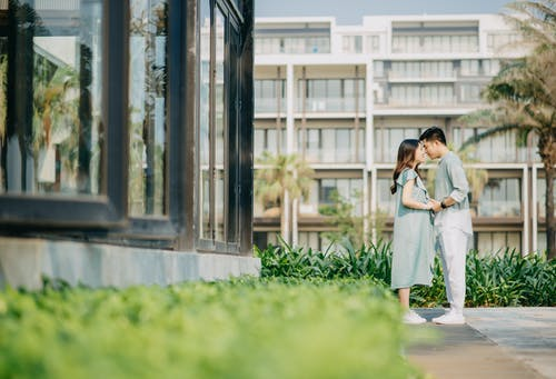 Side view of enamored young Asian couple in trendy outfits holding hands and smiling while standing together in tropical park near modern building during romantic holidays