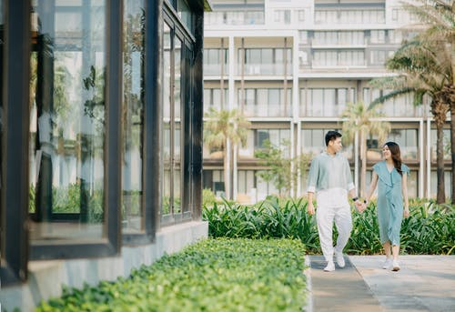 Full body of happy ethnic couple holding hands and strolling near contemporary buildings while looking at each other in summer