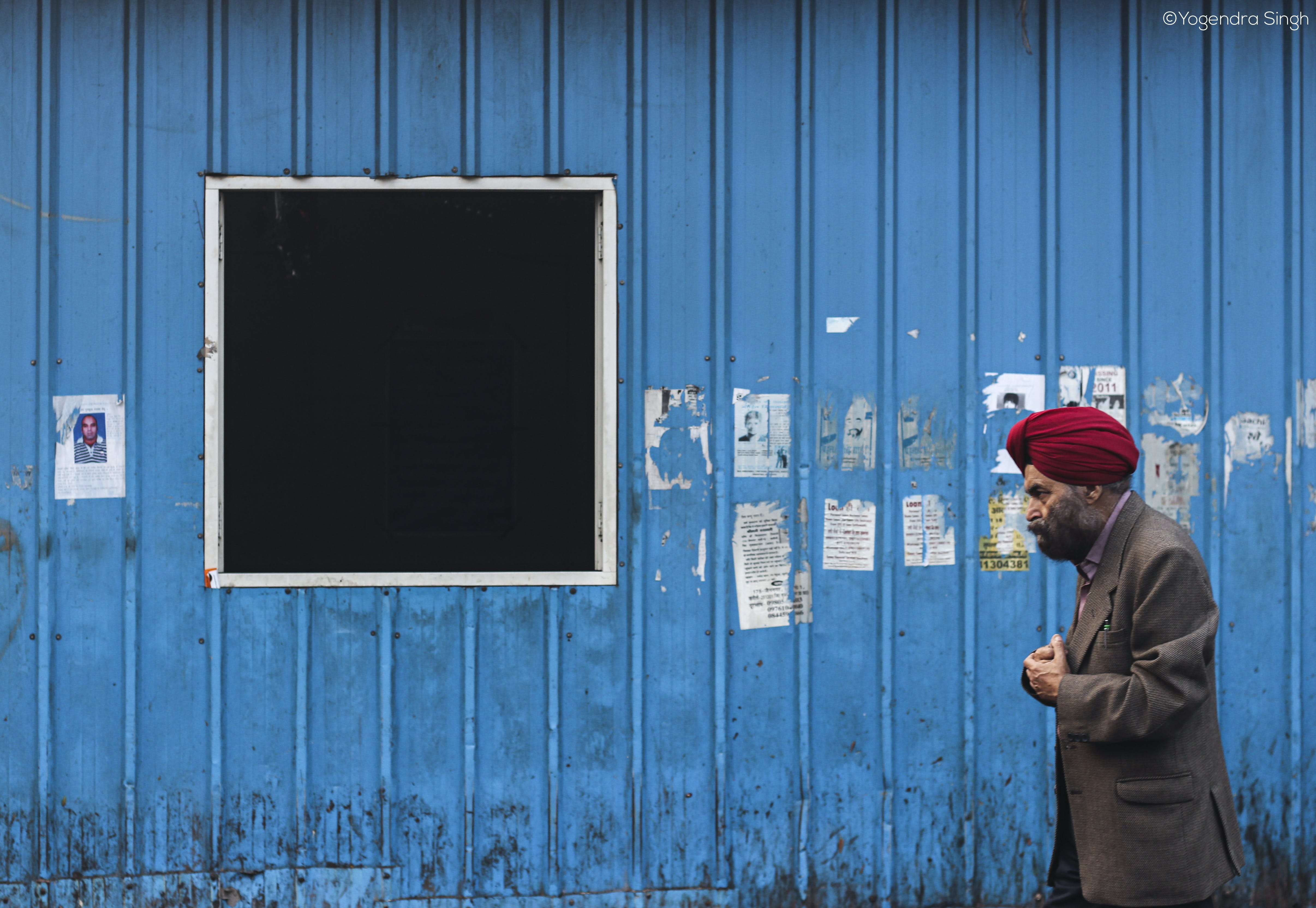 Man Walking Beside Blue Wall