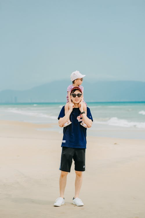 Asian father with cute child on shoulders on seashore