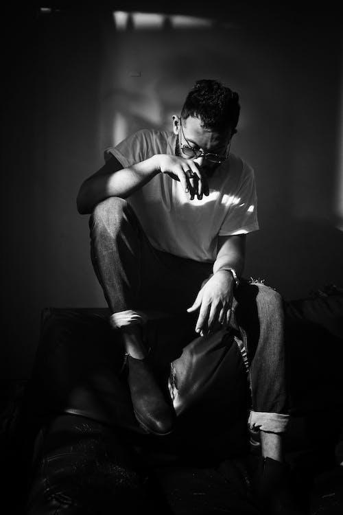Man in White Crew Neck T-shirt Sitting on Black Sofa