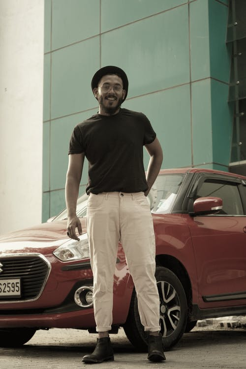 Man in Black Crew Neck T-shirt and Beige Pants Standing Beside Red Car