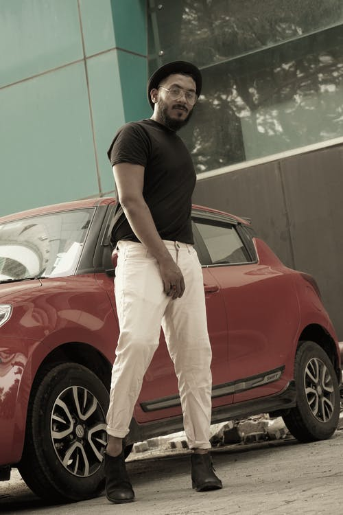 Man in Black Crew Neck T-shirt and White Pants Leaning on Red Car
