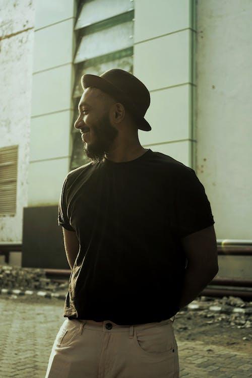 Man in Black Crew Neck T-shirt Wearing Black Cap