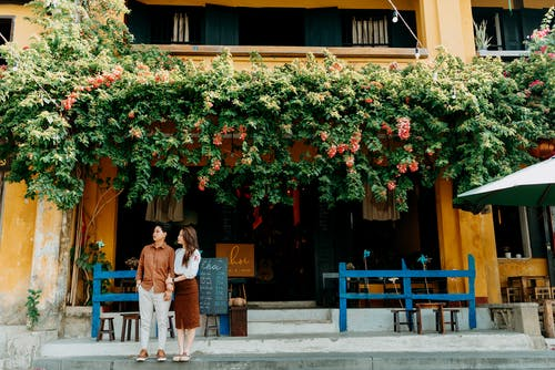 Full body of young romantic Asian couple wearing casual clothes and standing together near entrance of cafe decorated with blooming greenery