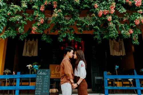Side view of romantic young Asian couple in trendy clothes holding hands and touching noses while standing near entrance of cozy cafe in city