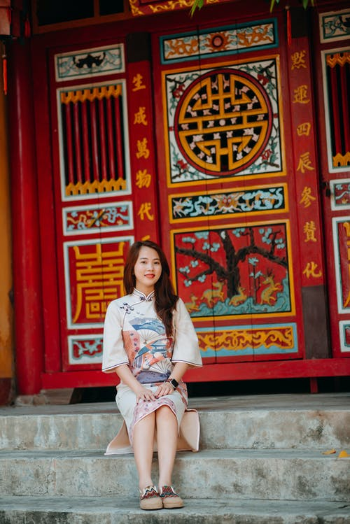 Smiling young Asian woman sitting on stairs of Buddhist temple