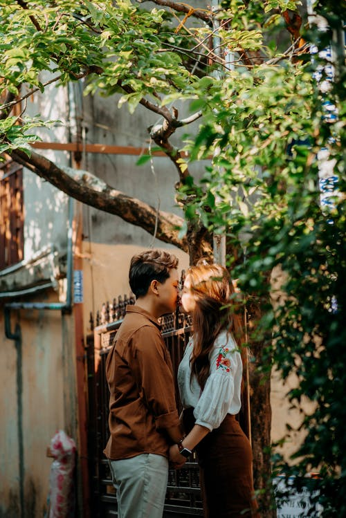 Enamored young Asian couple holding hands and kissing on street in sunlight
