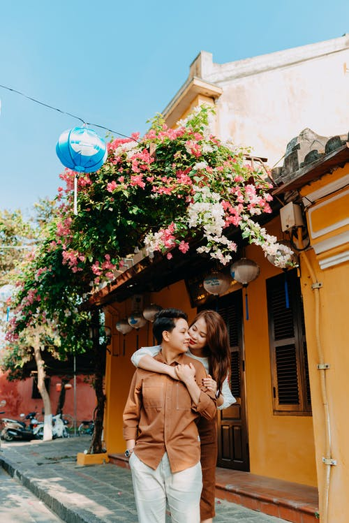 Stylish young ethnic lady with long brown hair embracing back of enamored boyfriend while standing together near small house decorated with blooming plants against cloudless blue sky in town