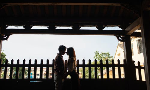 Amorous young Asian couple holding hands on terrace