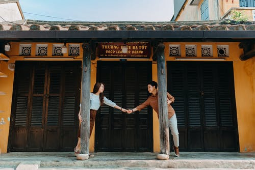 Joyful ethnic couple holding hands and looking at each other near old house