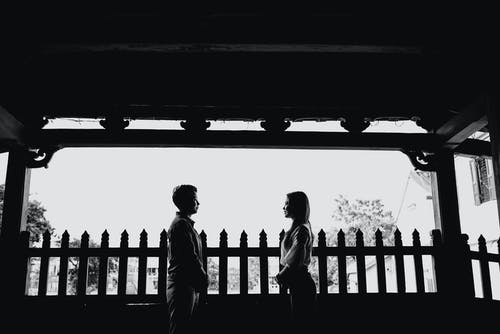 Positive young ethnic couple smiling and looking at each other on veranda