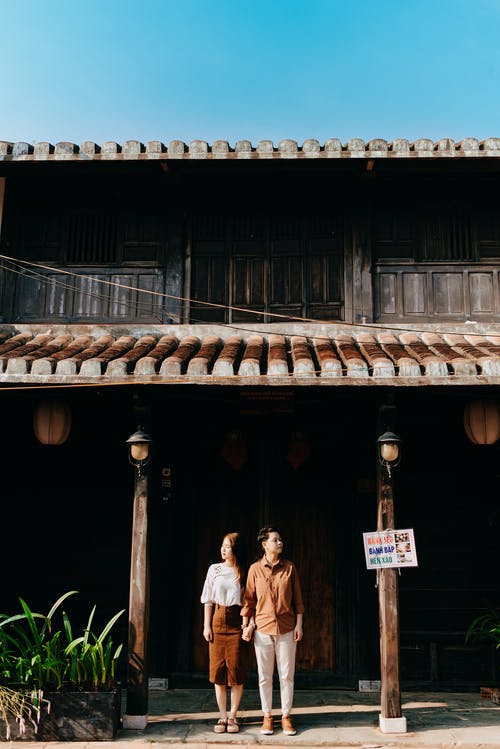 Full length of young ethnic couple in stylish clothes holding hands and looking in different directions while standing together near aged wooden house on sunny day