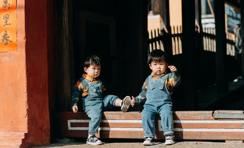 2 Boys Sitting on Brown Wooden Bench