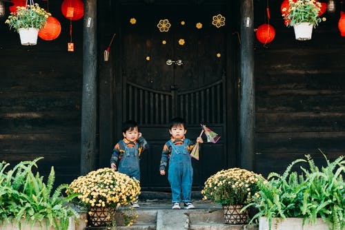 2 Boys and Girl Standing on Gray Concrete Pathway Near Brown Wooden Door