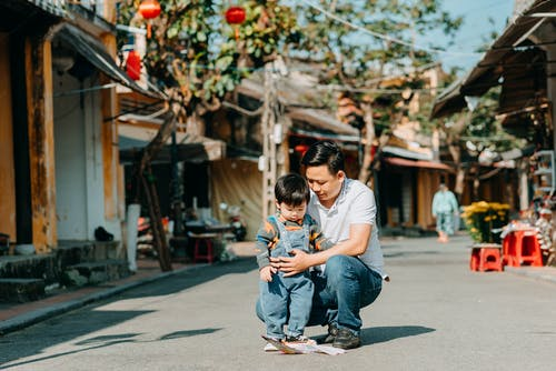 Man in White T-shirt Carrying Boy in Blue Denim Jeans