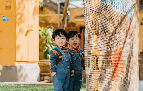Boy in Blue Denim Jacket Standing Beside Brown Wooden Fence