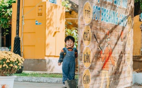 Boy in Blue Denim Jacket Standing Beside Brown Wooden Wall