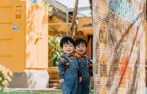 Boy in Blue Denim Jacket Standing Beside Brown Metal Fence