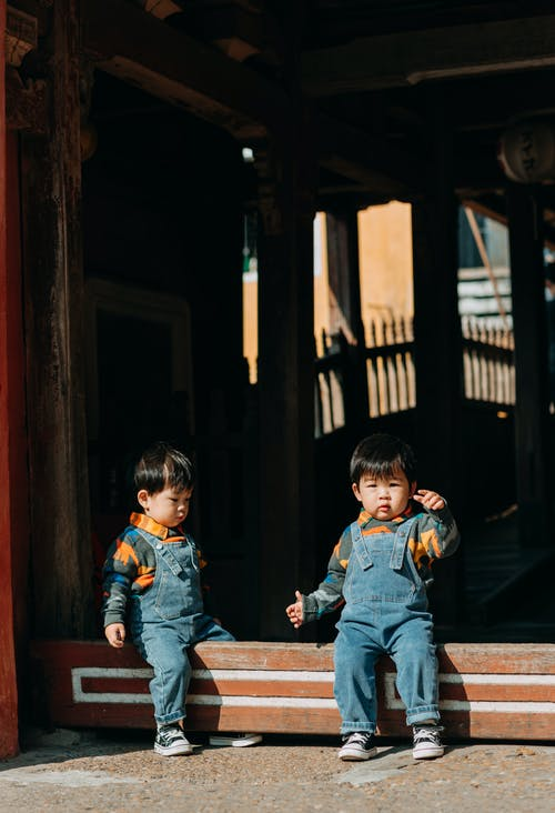 2 Boys Sitting on Brown Wooden Fence