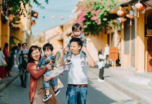 Woman in White Shirt Carrying Girl in Blue Shirt