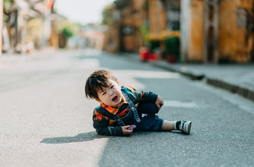 Boy in Black and Red Jacket Sitting on Road
