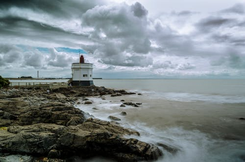 White Lighthouse on Brown Rocky Shore Under White Cloudy Sky