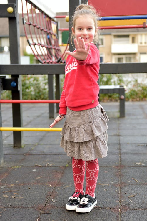 Girl in Red Long Sleeve Shirt and Gray Skirt Standing on Playground