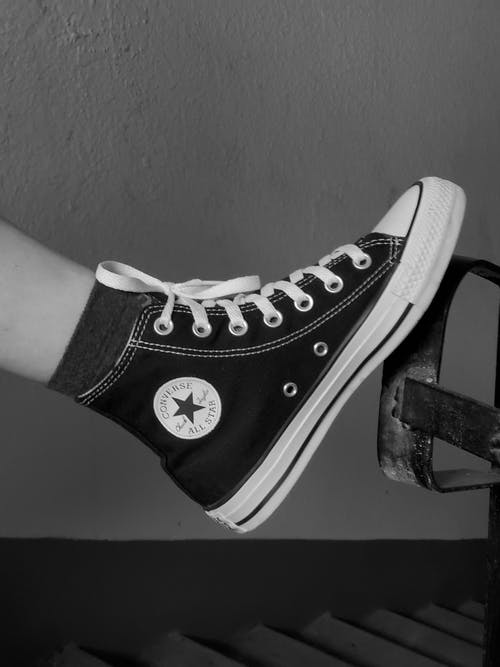 Grayscale Photo of a Person Wearing Converse Shoes