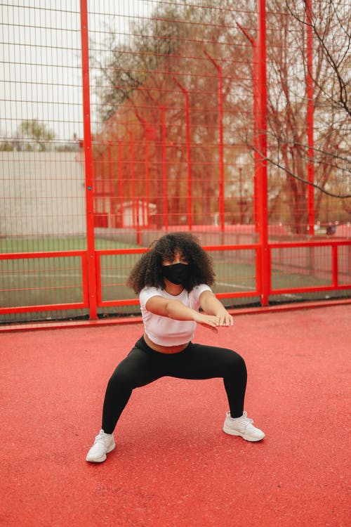 A Woman Exercising while Wearing a Face Mask