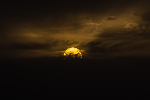 Photography of Moon Behind Clouds