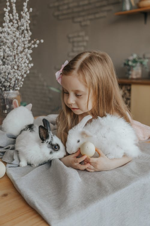 Adorable little child lying on table with eggs and fluffy bunnies during Easter holiday at home
