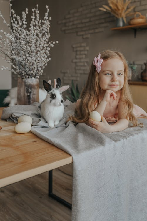 Adorable girl lying on table with rabbit and Easter eggs