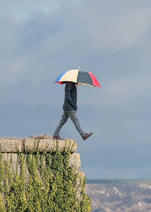 Бесплатное стоковое фото с высота, гуляя человек, зонтик, облачное небо