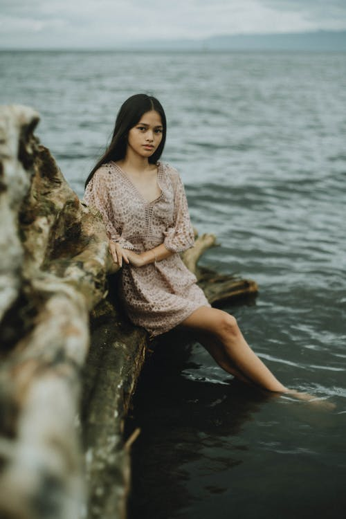 Woman in Pink Dress Sitting on Rock by the Sea