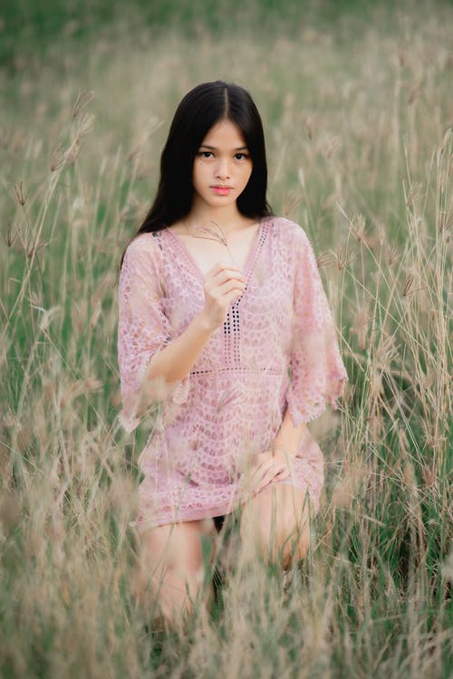 Woman in Pink and White Floral Dress Standing on Green Grass Field