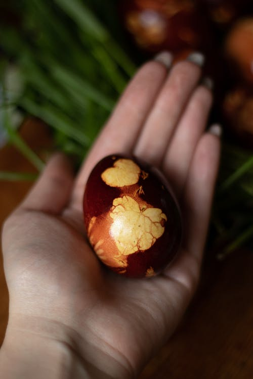 Top view of crop anonymous person demonstrating decorating Easter egg on blurred background
