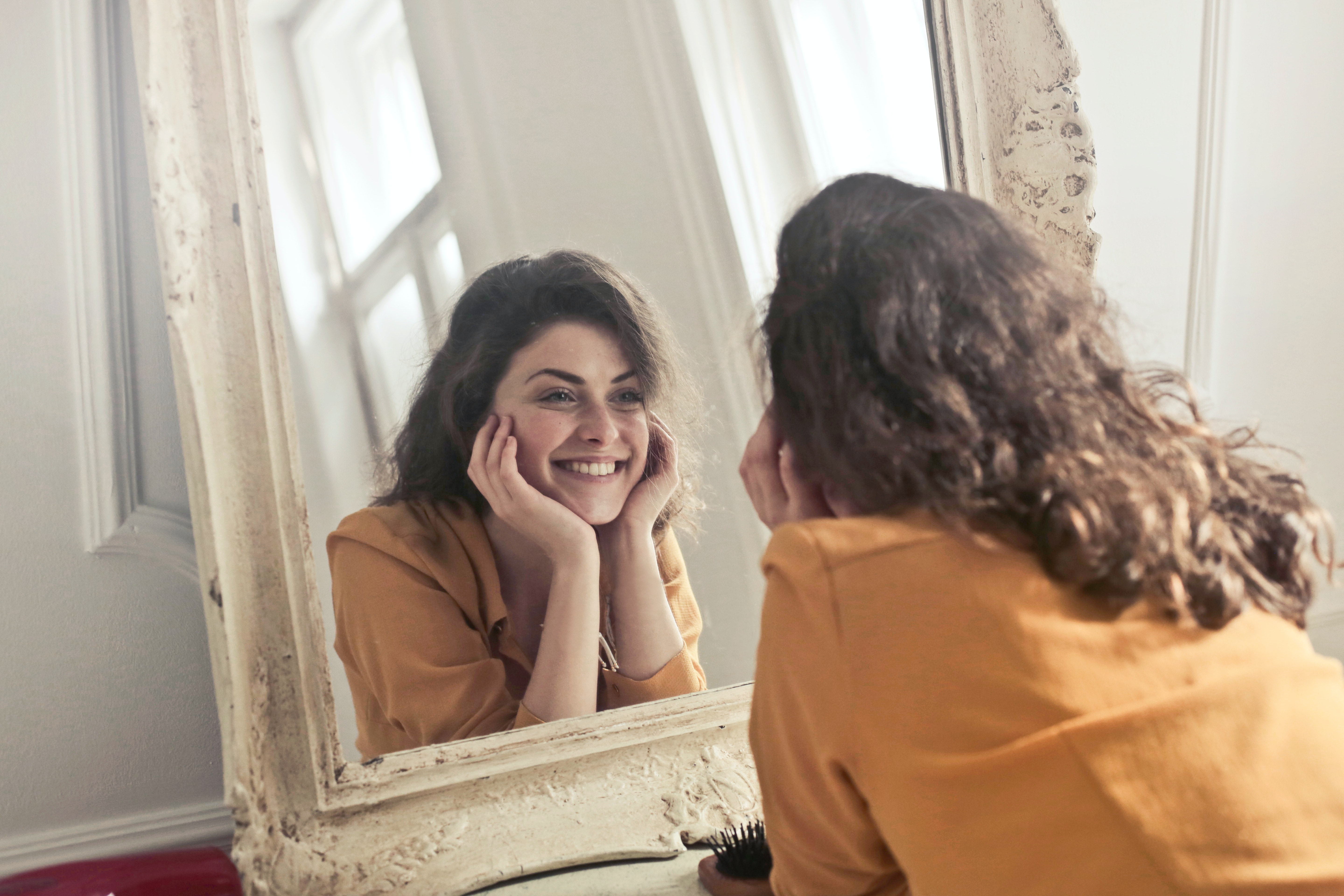 photo of woman looking at the mirror free stock photo