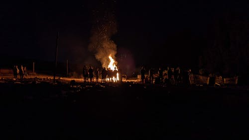 People Standing Near Bonfire during Night Time