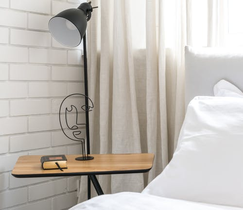Wooden Side Table and Floor Lamp Beside a Bed