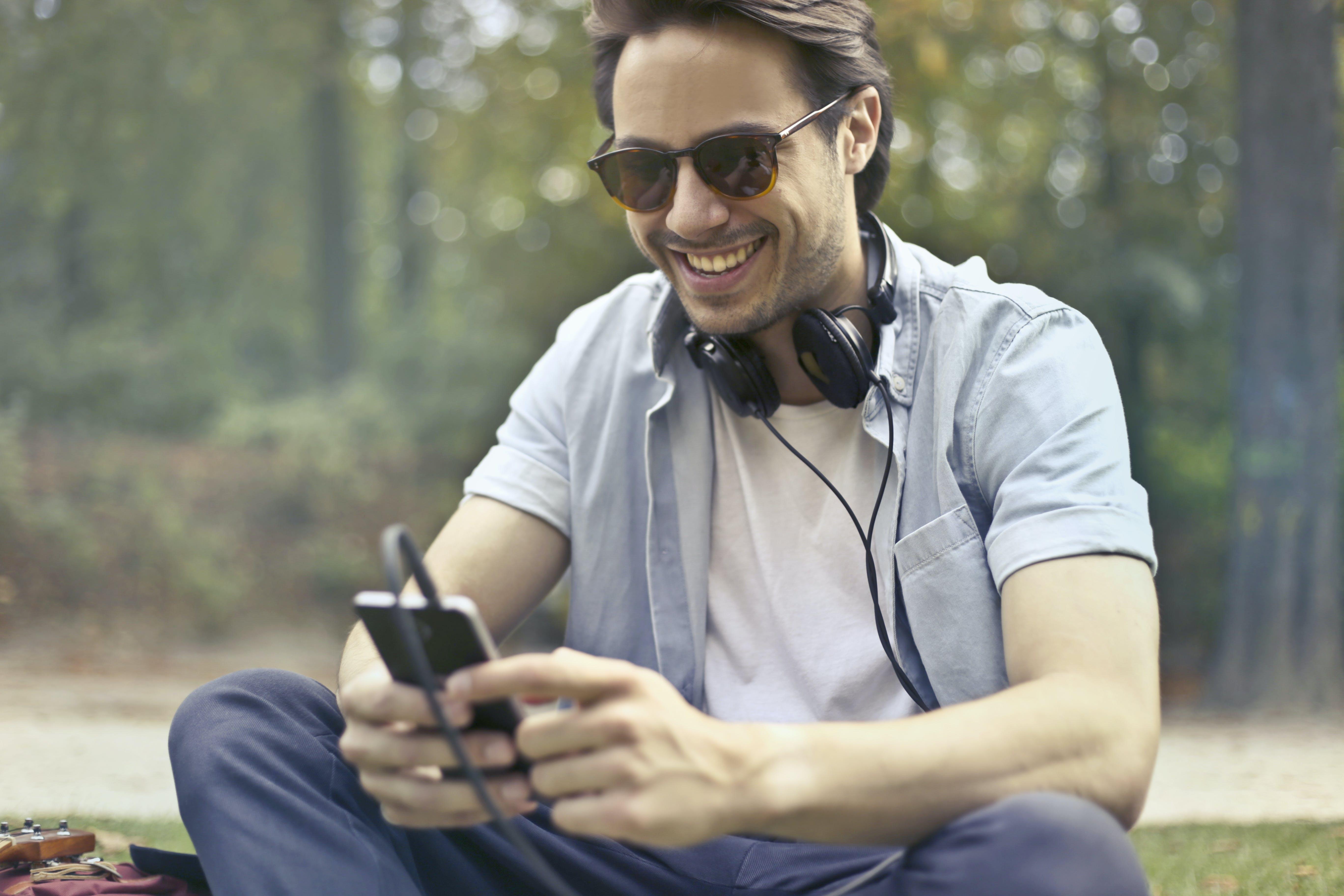 Man Wearing Sunglasses Using Smartphone at Daytime