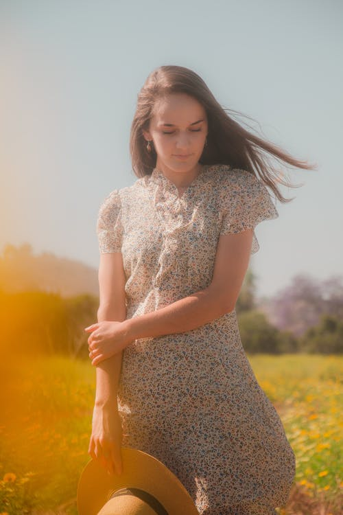 Woman in White Floral Dress Standing on Yellow Grass Field
